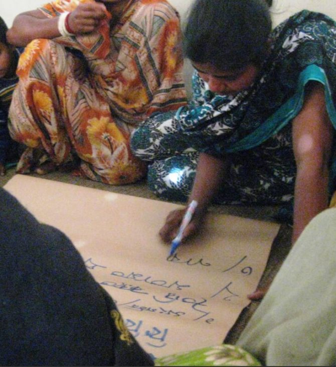 Members of an organization of Santal women write down ideas for diversifying their income opportunities