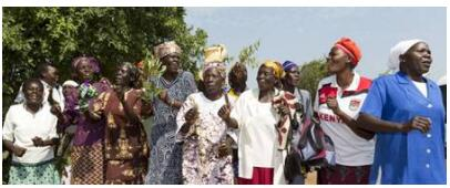 Women sing to greet a foreign delegation in a village in Kenya